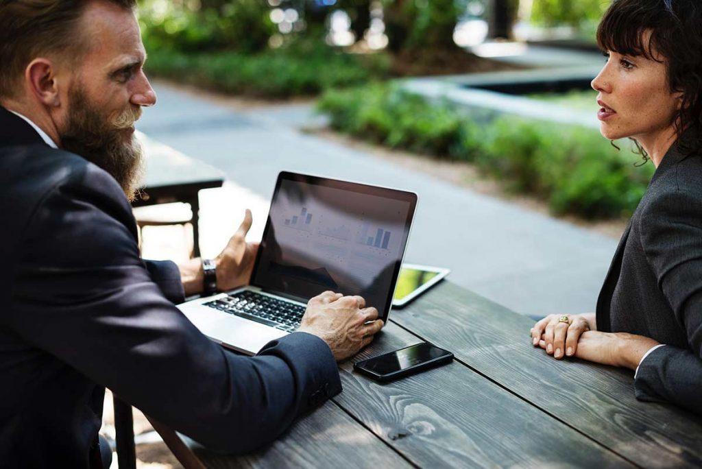 Hombre en traje, frente a computador, hablando seriamente con mujer ejecutiva