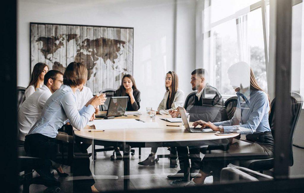 Grupo diverso de personas sentadas al rededor de una mesa, en una reunión