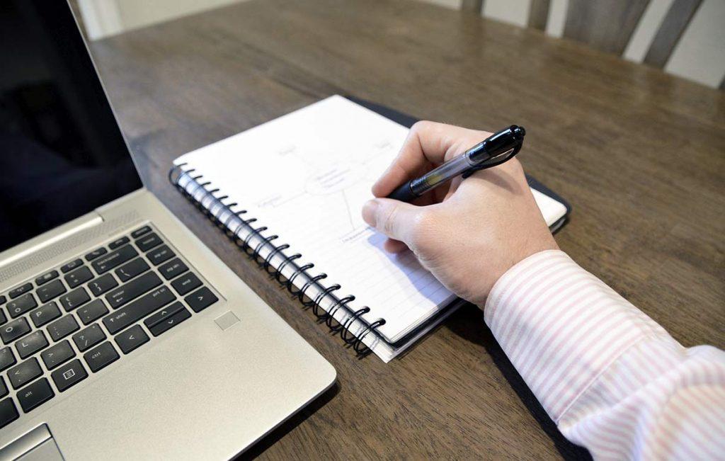 Brazo escribiendo en un cuaderno, sobre un escritorio con computador